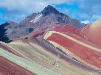 very zoomed in photo of Rainbow Mountain and another mountain peak with the red color intertwined